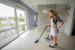 Beautiful blond woman vacuuming living room. Royalty Free Stock Photo