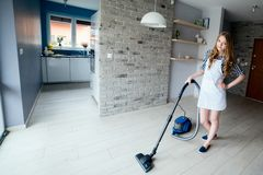 Beautiful blond woman vacuuming living room. Wide angle. Beautiful blond woman vacuuming living room. She is wearing a white apron. Wide angle Stock Photos