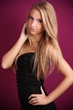 Beautiful blond woman with violet background. Beautiful blonde in a black dress, studio photo on violet background, she has her hand on her hips and the second Royalty Free Stock Images