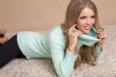 Beautiful blond woman in warm sweater lying on carpet Stock Images