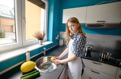 Beautiful blond woman washing fruit. Royalty Free Stock Photos
