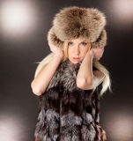 Beautiful blond woman wearing fur coat. Portrait of a beautiful blond woman wearing fur coat and hat Royalty Free Stock Images
