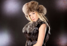 Beautiful blond woman wearing fur coat Stock Photos