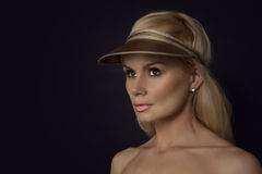 Beautiful blond woman wearing a gold peak Royalty Free Stock Images