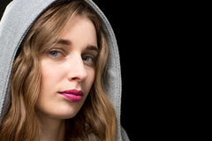 Beautiful blond woman wearing a hood. Close up face portrait of a beautiful blond woman wearing a hood looking at the camera with a thoughtful serious expression Stock Photography