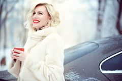 Beautiful blond woman wearing luxurious white fur coat drinking hot coffee on snowy winter day and laughing stock photography
