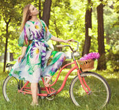 Beautiful blond woman wearing a nice dress having fun in park wi Stock Image