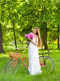 Beautiful blond woman wearing a nice dress having fun in park wi Stock Photos