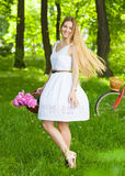 Beautiful blond woman wearing a nice dress having fun in park wi Stock Images