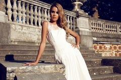 Beautiful blond woman wears wedding dress,posing beside antic villa Stock Photo