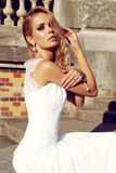 Beautiful blond woman wears wedding dress,posing beside antic villa Stock Image