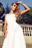Beautiful blond woman wears wedding dress,posing beside antic villa Royalty Free Stock Images