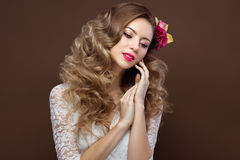 Beautiful blond woman in wedding dress with evening make-up, tender lips and curls. Bride image. Beauty face. Stock Photo