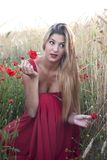 Beautiful blond woman in a wheat field with poppies at sunset Royalty Free Stock Photo