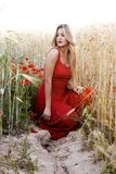 Beautiful blond woman in a wheat field with poppies at sunset Stock Images