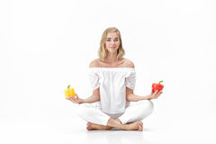 Beautiful blond woman in white blouse chooses yellow or red bell pepper. Health and Diet. Beautiful blond woman in a white blouse chooses a yellow or red bell stock photography