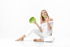 Beautiful blond woman in white blouse eating fresh green salad on white background. Health and Diet Royalty Free Stock Image