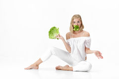 Beautiful blond woman in white blouse eating fresh green salad on white background. Health and Diet Royalty Free Stock Photo