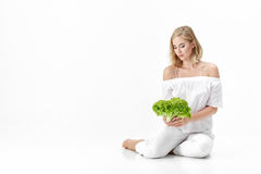 Beautiful blond woman in white blouse holding fresh green salad on white background. Health and Diet Royalty Free Stock Photography