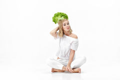 Beautiful blond woman in white blouse holding fresh green salad on white background. Health and Diet Stock Photography