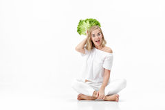 Beautiful blond woman in white blouse holding fresh green salad on white background. Health and Diet Stock Image
