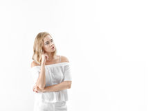 Beautiful blond woman in white blouse and pants on white background. copy spase Royalty Free Stock Image