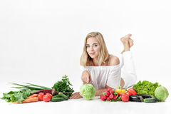 Beautiful blond woman in white clothes and lots of fresh vegetables on white background Royalty Free Stock Image
