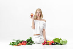 Beautiful blond woman in white clothes and lots of fresh vegetables on white background. girl is eating nectarine Stock Photography