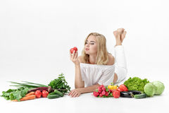 Beautiful blond woman in white clothes and lots of fresh vegetables on white background. Girl holding tomato Stock Images