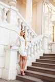 Beautiful blond woman in white dress on the stairs Royalty Free Stock Images