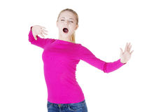 Beautiful blond woman yawning and stretching Royalty Free Stock Image