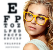 Beautiful blond woman with yellow trendy glasses. On the background of eye test chart Royalty Free Stock Photos