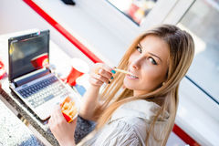 Beautiful blond young business woman sitting at table in restaurant or coffee shop with laptop computer eating delicious fries Royalty Free Stock Images