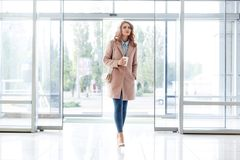 Beautiful blond young girl in a beautiful beige coat, jeans and high heels. Royalty Free Stock Images