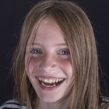 Beautiful blond young girl with freckles indoors on black background, closeup portrait royalty free stock photo