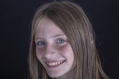 Beautiful blond young girl with freckles indoors on black background, closeup portrait royalty free stock photos