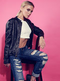 Beautiful blond young model posing in black leather jacket and b Royalty Free Stock Photography