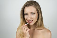 Beautiful blond young smiling woman putting lipstick on close up isolated white background stock photos
