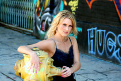 Beautiful blond young woman. Portrait of a gorgeous blond young woman against a wall of graffiti, leaning on a fire hydrant Stock Photography