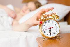 Beautiful blond young woman blocking alarmclock off wake up time & looking at clock on light copy space background Stock Photography