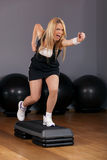 Beautiful Blond Young Woman Doing Step Aerobics in Royalty Free Stock Photo