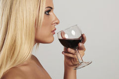 Beautiful blond young woman drinking red wine.girl with make-up.wineglass Stock Photo
