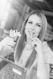 Beautiful blond young woman eating french fries in Royalty Free Stock Photo