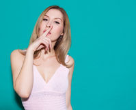 Beautiful blond young woman with a finger on her lips showing to keep silence, hush. Beauty girl in a pink dress having fun. Green Royalty Free Stock Photo
