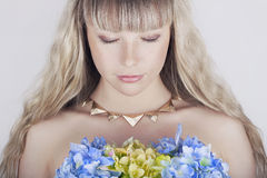 Beautiful blond young woman with flowers Royalty Free Stock Photos