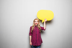 Beautiful blond young woman holding yellow blank speech bubble over grey background Royalty Free Stock Image