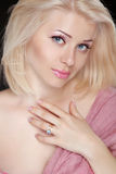 Beautiful blond young woman with pretty makeup, posing at camera Royalty Free Stock Photography