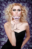 Beautiful blond young woman with purple cocktail on a floral background Stock Photography