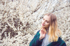 Beautiful blond young woman standing in front of wonderful bloom Royalty Free Stock Images
