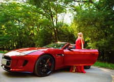 Beautiful blond young woman standing near a sports car. In a long red dress Stock Image